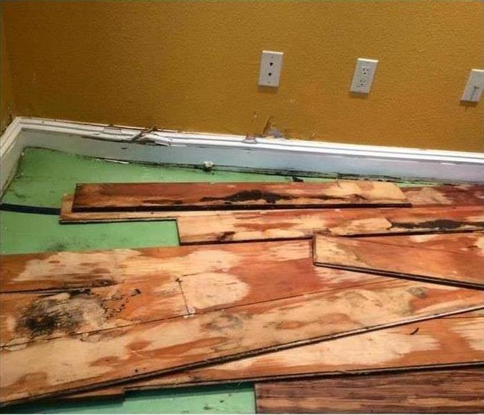 Multiple moldy floorboards piled on top of each other after a water damage cleanup.