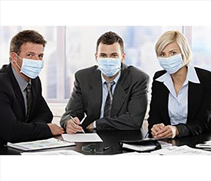 Three coworkers with face masks to protect from unhealthy air conditions.
